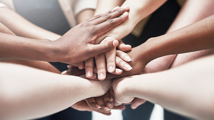 Diverse group of hands coming together in unity