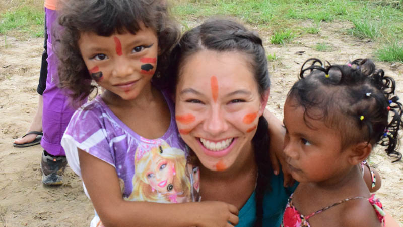 Student with children with paint on faces