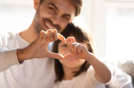 Family members form a heart with their hands.