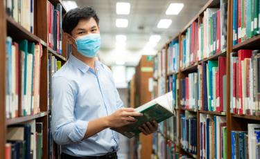 asian male student with mask on in library