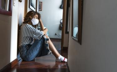 concerned woman sitting at home wearing a mask