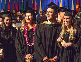 graduates smiling to commencement crowd