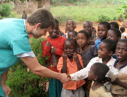 Partners and Services Sites - Physician with children in Africa