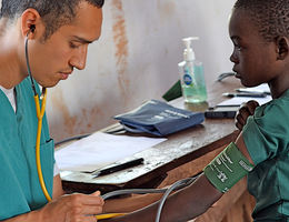 Physician taking blood pressure of child