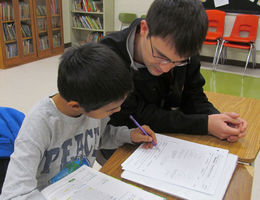 Student helping child with homework