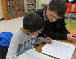 Student helping child in classroom