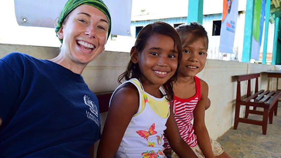 Student smiling with children from Belize